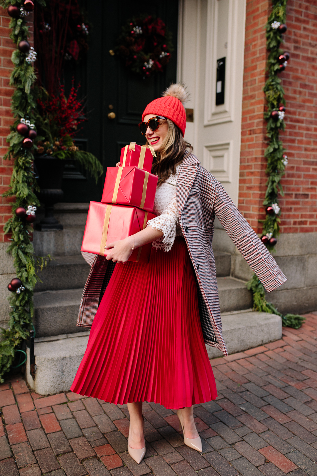 Boston Blogger, Kerrie M. Burke, wears a red midi skirt with a plaid coat